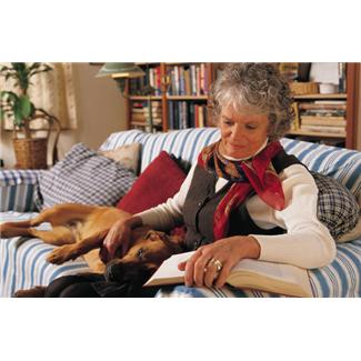 an older lady reading with her dog next to her